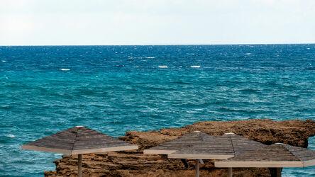 Bild mit Felsen, Horizont, Wellen, Meerblick, Meer, türkises Wasser, Naturfotografie, Sonnenschirme